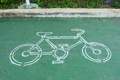 White bike symbol on the green pavement in Thailand. White bike symbol on the green pavement in Thailand Stock Photo