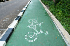 White bike symbol on the green pavement in Thailand. White bike symbol on the green pavement in Thailand Royalty Free Stock Images