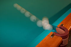 White Billiard Ball in Pocket. Time lapse of the cue ball, a white billiard ball, flying into the side pocket of a pool table Royalty Free Stock Photo