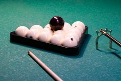 White billiard balls folded in a triangle on a green gaming table royalty free stock images