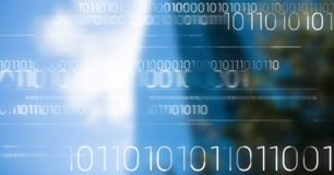 White binary code against blurry building. Digital composite of White binary code against blurry building Royalty Free Stock Image