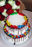 White Birthday cake with colorful Sprinkles over a light background with a bouquet of roses royalty free stock photos