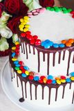 White Birthday cake with colorful Sprinkles over a light background with a bouquet of roses royalty free stock photo
