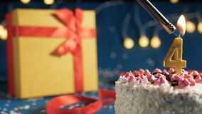 Free White Birthday Cake Number 4 Golden Candles Burning By Lighter, Blue Background With Lights And Gift Yellow Box Tied Up With Red Royalty Free Stock Image - 172384486