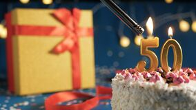 Free White Birthday Cake Number 50 Golden Candles Burning By Lighter, Blue Background With Lights And Gift Yellow Box Tied Up With Red Stock Images - 172385304