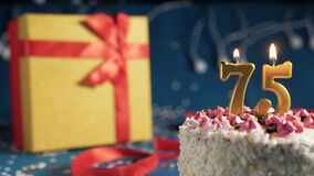 White birthday cake number 75 golden candles burning by lighter, blue background with lights and gift yellow box tied up with red