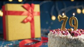 White birthday cake number 79 golden candles burning by lighter, blue background with lights and gift yellow box tied up with red