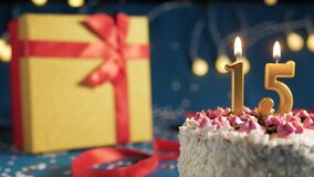 White birthday cake number 15 golden candles burning by lighter, blue background with lights and gift yellow box tied up