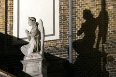 White and black angels. Angel statue with black angel shadow stock photography