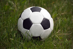 White and black ball for playing soccer in high green grass closeup Royalty Free Stock Photography