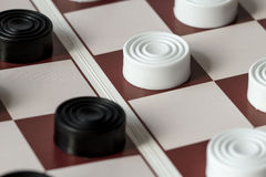White and black checkers on gaming board Royalty Free Stock Image