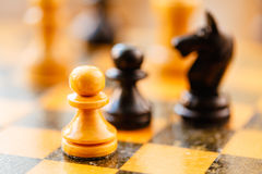 White and black chess pawns and knight standing on chessboard Stock Images