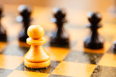 White and black chess pawns standing on chessboard Stock Image