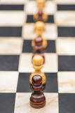 White and black chess pieces on a chessboard Stock Image