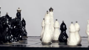White and black chessfigures scattered around the board stock video