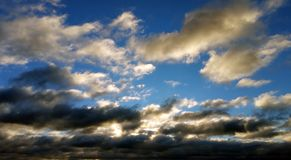 White and black clouds against blue sky at sunset Stock Images