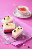 White and Black Currant Mousse Cakes. And cup of fruit tea, on a purple background Royalty Free Stock Photography