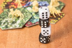 White and black dice on each other. On a blurred background of objects for table games Royalty Free Stock Photos