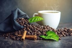 White black espresso Cup with pile of coffee beans and green leaves in bag on dark background. The concept of the production of fresh aromatic drink Stock Photography