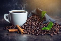 White black espresso Cup with pile of coffee beans and green leaves in bag on dark background. The concept of the production of fresh aromatic drink Royalty Free Stock Photography