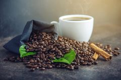 White black espresso Cup with pile of coffee beans and green leaves in bag on dark background. The concept of the production of fresh aromatic drink Royalty Free Stock Images