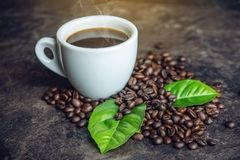 White black espresso Cup with pile of coffee beans and green leaves in bag on dark background. The concept of the production of fresh aromatic drink Stock Photos