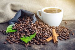 White black espresso Cup with a pile of coffee beans and green leaves in bag on white linen background. The concept of the production of fresh aromatic drink Royalty Free Stock Images