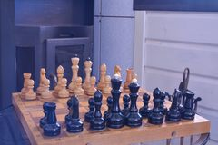 Chessboard with figures in front of the fireplace stock photos