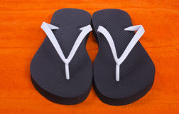 White and Black Flip Flop on Orange Beach Towel Royalty Free Stock Photography