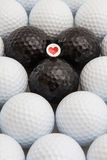 White and black golf balls and wooden tee Royalty Free Stock Images