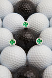 White and black golf balls and wooden tees. Different golf balls and wooden tees with four leaf clovers Royalty Free Stock Images