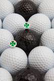 White and black golf balls and wooden tees. Different golf balls and wooden tees with four leaf clovers Royalty Free Stock Photos