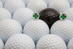 White and black golf balls and wooden tees. Different golf balls and wooden tees with four leaf clovers Royalty Free Stock Image