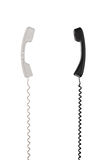 White and black handsets are arranged vertically towards each other. Royalty Free Stock Image