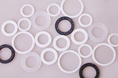White and black hydraulic and pneumatic o-ring seals of different sizes scattered a white background. Rubber rings. Sealing gaskets for hydraulic joints stock image