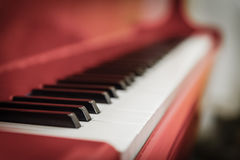 White and black keys of red piano. Closeup Royalty Free Stock Images