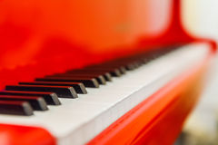 White and black keys of red piano. Closeup Stock Photo