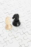 White and black knights and jigsaw puzzles Stock Images