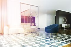 White and black living room corner, armchair toned. Modern living room with white and black walls, a tiled floor, a white sofa and a blue armchair. 3d rendering Royalty Free Stock Photos