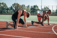 White and black male athletes are preparing to start stock images