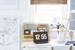Map, desk organizer and laptop. White and black map, wooden desk organizer and laptop with a clock set on a desk by the window royalty free stock photography