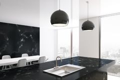 White and black marble kitchen side. White and black marble kitchen interior with large windows, a white table with chairs and a black marble countertop with a Royalty Free Stock Images