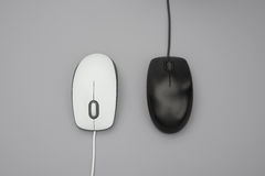 White and black mouses with cables on grey. Background stock photo
