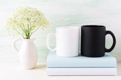 White and black mug mockup with books and white flowers Royalty Free Stock Images