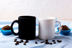 White and black mug mockup with coffee beans and muffins. Empty mug mock up for design presentation Royalty Free Stock Photos