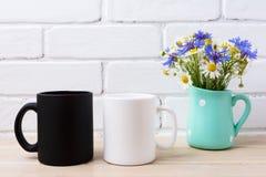 White and black mug mockup with cornflower and daisy stock photo