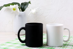 White and black mug mockup with lily in vase Royalty Free Stock Photo