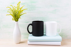 White and black mug mockup with ornamental green flowering grass Royalty Free Stock Photo
