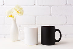 White and black mug mockup with soft yellow orchid in vase Stock Images