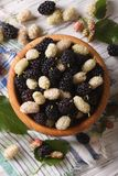 White and black mulberries in bowl close-up. vertical top view Royalty Free Stock Photography